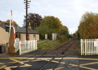 The level crossing at Oyne looking towards the station site on 16 October 2012. Although the telegraph poles are still standing the wires appear to have been removed in this area. At the next former station to the east, Pitcaple, 4 wires were still in place towards Inverurie. [See image 35899]<br><br>[John McIntyre&nbsp;16/10/2012]