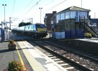 Coming out of the sun, the 09.30 ex-London Kings Cross runs north over Chathill level crossing on 8 October 2012. This train operates non-stop between Alnmouth (13.10) and Waverley (14.15). <br><br>[John Furnevel&nbsp;08/10/2012]