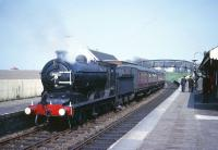 Class J37 0-6-0 no 64602 at the head of a southbound railtour from Dundee stands at Anstruther station on the Fife Coast line in the early 1960s. Part of the tower and flagpole of Waid Academy can be seen beyond the station canopy on the right. <br><br>[Robin Barbour Collection (Courtesy Bruce McCartney)&nbsp;//]