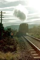 The track gang stands clear as the afternoon train from Aviemore to Boat of Garten comes out of the sun in the summer of 1980. [With thanks to John McIntyre] <br>  <br><br>[Colin Miller&nbsp;//1980]