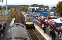 Class 170s cross at Dyce on 19 October 2012. On the left is a service for Inverness while approaching on the right is a service to Edinburgh. Raiths Farm yard is beyond the overbridge in the background and to the left of the running line.<br><br>[John McIntyre&nbsp;19/10/2012]