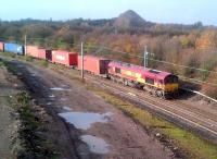 A container train takes the link from the Birmingham line to the WCML  at Nuneaton on 14 November. The spoil heap in the background is the waste tip from (the formerly rail-served) Judkins quarry. It is now adjacent to the local 'recycling facility' and can be seen from miles around. Meanwhile, the catenary seen here will eventually be extended to Whitacre Junction and Birmingham.<br><br>[Ken Strachan&nbsp;14/11/2012]