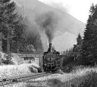 Scene on the 13 km long rack worked line through the Styrian Alps from Vordernberg to Erzberg, used to transport iron ore from the workings at Erzberg. Here 0-6-2RT No. 97.205 (with sister locomotive 97.204 at the rear) approaches Glaslbremse in September 1975 with the 14.10 empties from Vordernberg. The locos are about to enjoy a brief respite from climbing on the level section through Glaslbremse halt.<br><br>[Bill Jamieson&nbsp;06/09/1975]