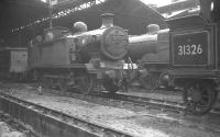 Wet day at Nine Elms. Locomotives in the shed yard at 70A on 21 August 1961 include E2 0-6-0T no 32102, with the rear end of H class 0-4-4T no 31326 nearest the camera. Both locomotives were withdrawn by BR in October that year.<br><br>[K A Gray&nbsp;21/08/1961]