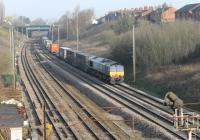 Bright spring sunshine as DRS 66423 takes a long container train along the Up Fast line at Farington Curve Junction in March 2012.<br><br>[Mark Bartlett&nbsp;22/03/2012]