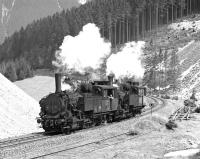 Having taken the 11.20 half load of iron ore from Erzberg to the summit station at Pr�bichl, conventional chimneyed 0-6-2RT No. 97.207 and Giesl fitted No. 97203 drift downhill at Feistawiese on 15 April 1976 on their way to pick up the second portion. <br><br>[Bill Jamieson&nbsp;15/04/1976]