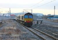 After a night when nearby Shap was the coldest place in the UK (at -7C), a late running <I>Stobart Tesco Express</I> is diverted into the Down loop at a very frosty Penrith to allow two passenger services to overtake. DRS 66421 and 66423 were in charge of the train, the rear of which can be seen above the siding buffers to the right of 66421. <br><br>[Mark Bartlett&nbsp;30/11/2012]
