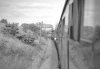 View from a carriage window of the RCTS (West Riding Branch) <i>Borders Railtour</i> near Coldstream on 9 July 1961. NBR 4-4-0 no 256 <I>Glen Douglas</I> + J37 0-6-0 no 64624 are taking the special as far as Tweedmouth, where A1 Pacific no 60143 <I>Sir Walter Scott</I> will take over for the journey south to Newcastle via the ECML. [See image 30192]<br> <br> <br><br>[K A Gray&nbsp;09/07/1961]