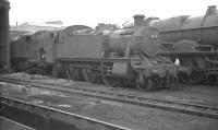 Collett 2-6-2T no 4165 in the yard at Wolverhampton's Stafford Road shed in August 1962, looking slightly intimidated by King class 4-6-0 no 6012 <I>King Edward VI</I> standing alongside. The tank engine survived for another 3 years, although the 'King' was withdrawn one month after the photograph was taken.<br><br>[K A Gray&nbsp;15/08/1962]