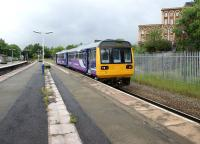 A Northern Class 142 arrives at Wigan Wallgate with a service to Manchester Victoria on 16 June 2012. The view is west and the embankment and overbridge carrying the WCML can be seen in the left background.<br><br>[John McIntyre&nbsp;16/06/2012]