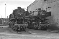 Oil-fired 2-10-0s 043 737 and 043 087 stabled next to the roundhouse at Rheine in 1974. 043 737 was a product of the French firm Batignolles, built in 1944, while 043 087's origins were more what might be expected - the German firm of Henschel, emerging from the Kassel works in 1937. <br> <br><br>[Bill Jamieson&nbsp;07/09/1974]