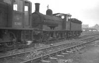 Class J21 0-6-0 no 65099 and BR 0-6-0DM no D2053 stand together in the sidings at the north end of Darlington shed awaiting admission to the nearby locomotive works. The photograph was taken in late 1961, shortly after 65099 had been withdrawn from Tyne Dock, having been identified as a potential preservation candidate. [See image 26302]<br><br>[K A Gray&nbsp;//1961]