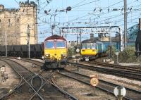 Platform view from the east end of Newcastle Central in July 2004. EWS 66229 is approaching with a coal train from the north with a DMU coming off the High Level Bridge. The Castle Keep stands on the left, while the north end of the Tyne Bridge can be seen in the right background.<br><br>[John Furnevel&nbsp;06/07/2004]