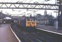 A double-headed eastbound freight trundles through Guide Bridge in 1978 with 76030 in the lead. The <I>Tommies</I> are on the now lifted tracks while over on the right, Class 40 40134 waits for a green signal with a Ford container train. The buildings in this view, and the footbridge, have since disappeared and the area between the platforms has been filled in leaving only the other two lines still active. <br><br>[Mark Bartlett&nbsp;//1978]