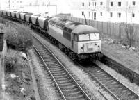 A Class 56 brings coal empties round the Edinburgh 'sub' in 1982. The train is about to pass eastbound through the remains of Morningside Road station with building work underway in the background on the site of the former goods yard.<br><br>[John Furnevel&nbsp;11/11/1982]