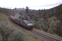 Just north of Grantown-on-Spey, a BRCW Type 2 hauled train drifts down the gradient from Dava Summit, not long after the 1958 start of dieselisation in the Highlands. <br><br>[Peter Oliver Collection (Courtesy David Spaven)&nbsp;//1958]