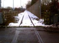The mud, grass, and snow on the rails tell a sad story of non-use in this view looking ESE towards Coventry City's Ricoh Stadium, just visible on the skyline [see image 35643]. The Stadium station is now due to be built in 2014. A second pair of rails is set in the tarmac to the left of this crossing, at the evocative-sounding junction of Winding House Lane and Wheelwrights Lane.<br><br>[Ken Strachan 26/01/2013]
