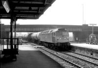 Bescot class 47 no 47386 brings a train of 100t oil tanks under Coronation Bridge and north through Rotherham Masborough station in May 1981. The station finally closed in October 1988.<br><br>[John Furnevel&nbsp;04/05/1981]