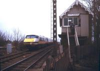 A diverted ECML electric train bound for Kings Cross being dragged through Littleworth station (closed to passengers in 1961) on the GN line between Peterborough and Spalding. View south from the A16 level crossing in January 1991. <br><br>[Ian Dinmore&nbsp;/01/1991]