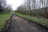 Ongoing work in February 2013 involving the upgrading of the cycle track which nowadays replaces the the siding that once ran from East Kilbride Station to Mavor and Couson's engineering works at Nerston. The line which was just under a mile in length closed in 1966. The boundary wall of East Kilbride Juniors football club is on the right, while garden walls of houses in the East Mains area of the town are on the left. [See image 19670]<br><br>[John Steven&nbsp;22/02/2013]