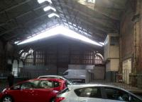 Brunel's original train shed at Temple Meads in February 2013. The site is now used for car parking (with a �1 discount for parking outdoors!), but should soon be reopened as a terminus for electric trains from London. Notice the signal box on the right.<br><br>[Ken Strachan 10/02/2013]