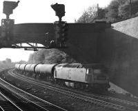 An unidentified Brush Type 4 brings an eastbound train of 100T bogie oil tanks under Addingford Lane Bridge at the west end of Horbury cutting. Thought to have been taken on 12th May 1977.<br><br>[Bill Jamieson&nbsp;12/05/1977]