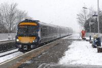 A northbound service pulls into Stonehaven station with easterly gale force winds driving snow in from the north sea on Sunday 10th March 2013. A Scotrail staff member is hard at work clearing snow and salting the platforms. <br><br>[Brian Taylor&nbsp;10/03/2013]