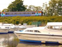 A 'Bittern Line' train passing Boats moored at Hoveton in 2006.<br><br>[Ian Dinmore&nbsp;//2006]