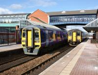 On the left a Class 158 calls at Barnsley Interchange on 12 March 2013 with a Sheffield to York fast service. On the right the Class 150 is on the Huddersfield to Sheffield via Penistone service. A smart station building with covered footbridge which links direct into the bus station on the left.<br><br>[John McIntyre&nbsp;12/03/2013]