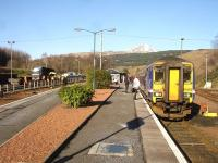 156493 stands at Crianlarich awaiting the Fort William portion on 19 February 2013. Over on the left steel sleepers are being off-loaded from a road vehicle in the goods yard.<br><br>[David Pesterfield&nbsp;19/02/2013]
