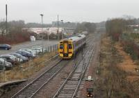 A Glasgow Queen Street - Falkirk Grahamston service, formed by unit 158718, pulls away from Cumbernauld station on 8 March 2013. The train is passing the turnback siding and crossover used by the Motherwell shuttles. <br><br>[Mark Bartlett&nbsp;08/03/2013]
