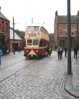 On a suitably dreich day, with wet cobbles glinting, passengers alight at the Beamish Town stop. A department store very familiar during the photographer's childhood is advertised on the front of the double deck tram.<br><br>[Brian Taylor&nbsp;02/04/2013]