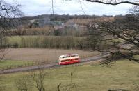 On-loan Blackpool 'Balloon' car 703, disguised as Sunderland tram 101, passes Pockerly Manor, Beamish, on its way to the authentically smoking Town in the background on 2 April 2013. [See image 42616]  <br><br>[Brian Taylor&nbsp;02/04/2013]