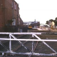 The west side of Bridlington station in 1988 looking towards Hull. The main station building is on the left and the gate gave access to the goods yard (now a car park and supermarket site). The DMU is at platform 4, with demolition work in progress around platforms 1 - 3 and the Station Road entrance. Housing now occupies the area beyond the wooden fence. [See image 23828]<br><br>[Ian Dinmore&nbsp;/09/1988]