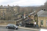 Saltaire station, seen from nearby Salt's Mill, as 333014 leaves for Keighley and Skipton. The station was closed from 1965 to 1984 but is now very busy and sees four trains per hour in each direction. Some of the houses at this world heritage site can be seen to the left of the station.<br><br>[Mark Bartlett&nbsp;19/04/2013]