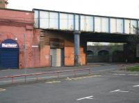 Looking north at the top of Molendinar Street in 2007, with Gallowgate behind the camera. The bridge carries the CGU line between Saltmarket Junction and High Street East Junction. Round the corner under the bridge is the former entrance to Gallowgate station (closed as long ago as 1902). In the right background on the north side of Bell Street is the urban viaduct that once carried the lines into College goods depot, the huge warehouse of which still stands as flats [see image 14886].<br><br>[John Furnevel&nbsp;06/05/2007]