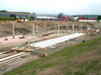 The Edinburgh Gateway tram stop under construction on 10 June 2013. View is east with Gogar roundabout and the Edinburgh tram depot behind the camera. On the upper level In the background the 11.21 Glenrothes with Thornton - Newcraighall service is passing through the site of the new station.<br><br>[John Furnevel&nbsp;10/06/2013]