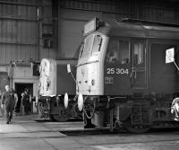 An open day at Carlisle Diesel Depot on 4th September 1976 finds BR Sulzer Type 2 No. 25304 stabled inside the shed adjacent to an unidentified class 40.<br><br>[Bill Jamieson&nbsp;04/09/1976]