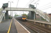 The 1407 Edinburgh Waverley - Manchester Airport arriving at Lockerbie on 11 June. The footbridge with integral lifts was commissioned in February 2008, prior to which passengers arriving from the north with impaired mobility and requiring assistance were advised to travel to Carlisle and change to a northbound stopping train.<br><br>[John Furnevel&nbsp;11/06/2013]