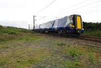 An Ayr-bound 380 unit passing the site of Lochgreen Junction at the south end of the Troon Loop on 29 June 2013. Photographed from the track-bed of the original direct line. [See image 28035] <br><br>[Colin Miller&nbsp;29/06/2013]