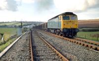 The severed link at Crediton in 1985. View west showing the disconnected double track to Newton St Cyres. The class 47 is hauling a Meldon Quarry to Exeter Riverside ballast train.<br><br>[Ian Dinmore&nbsp;//1985]