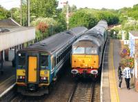 DRS 47802 brings a Great Yarmouth - Norwich train through Acle on 21 June 2011, passing a pair of class 153s waiting at the eastbound platform. DRS 47712 is on the rear of the train. [See image 43341]<br><br>[Ian Dinmore 21/06/2011]
