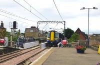 The 10.23 Ayr - Glasgow Central rolls into Prestwick station on 3 July over the newly installed replacement underbridge at the south end of the station.<br><br>[Colin Miller&nbsp;03/07/2013]