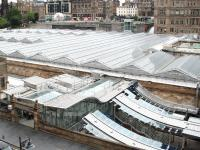 A touch of glass. View over Waverley towards Princes Street on 7 July 2013. Dominating the scene is a section of the recently reglazed station roof. In the foreground is the transformed Market Street entrance with work continuing on new access and replacement canopies for 'sub' platforms 8 & 9. In the background, immediately to the left of the Balmoral Hotel, is part of the glass roof covering Waverley Steps, with passenger lifts now operating alongside. <br><br>[John Furnevel&nbsp;07/07/2013]
