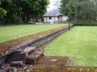 Looking from track level along the platform to the well maintained and occupied station building at the former Dornoch Station, showing both structures still intact 53 years after closure. <br><br>[David Pesterfield&nbsp;23/06/2013]