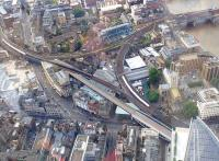View over Borough Market Junction on 20 July with trains on the Charing Cross / Blackfriars route (left) and the cross-Thames lines from Cannon Street. The new east-west viaduct seen under construction will enable quadrupling here, with the southern pair of lines handling trains to and from Charing Cross and the northern pair providing Thameslink trains with a dedicated route to Blackfriars - essential in providing the planned 24tph peak service on the route. London Bridge station is just off picture bottom right.<br><br>[John Thorn&nbsp;20/07/2013]