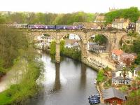 Looking east along the River Nidd at Knaresborough with a Northern DMU on the viaduct. The unique Knaresborough signal box [see image 23671] can be seen on the right of the picture. <br><br>[Ian Dinmore&nbsp;//]