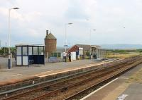 Three items of interest in this view of Seascale's southbound platform. The old Furness Railway water tower is a prominent local landmark. To its right is the old goods shed, which is now the town's Sports Centre. On the platform itself is a <I>Harrington Hump</I> which provides level access to trains. These were pioneered at the station of the same name, just north of Whitehaven, and provide a cost effective alternative to raising low platforms along their full length. They are appearing at various Cumbrian Coast stations and elsewhere in the UK. <br><br>[Mark Bartlett&nbsp;27/07/2013]