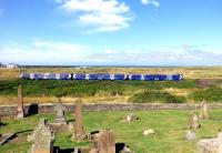 An Ayr to Glasgow Central class 380 service heads north, dead on schedule, shortly after calling at Prestwick Town on 30 July 2013. The graveyard of the 12th Century St Nicholas Church is in the foreground, with Old Prestwick Golf Course on the seaward side of the line. <br><br>[Colin Miller&nbsp;30/07/2013]