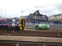 158703 stabled outside Inverness Depot on 24 June amidst much activity in the adjacent Stobart Rail facility as Tesco containers are unloaded.<br><br>[David Pesterfield&nbsp;24/06/2013]